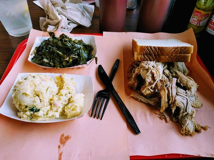 Rodney Scott's BBQ Whole hog BBQ plate with collard greens and potato salad